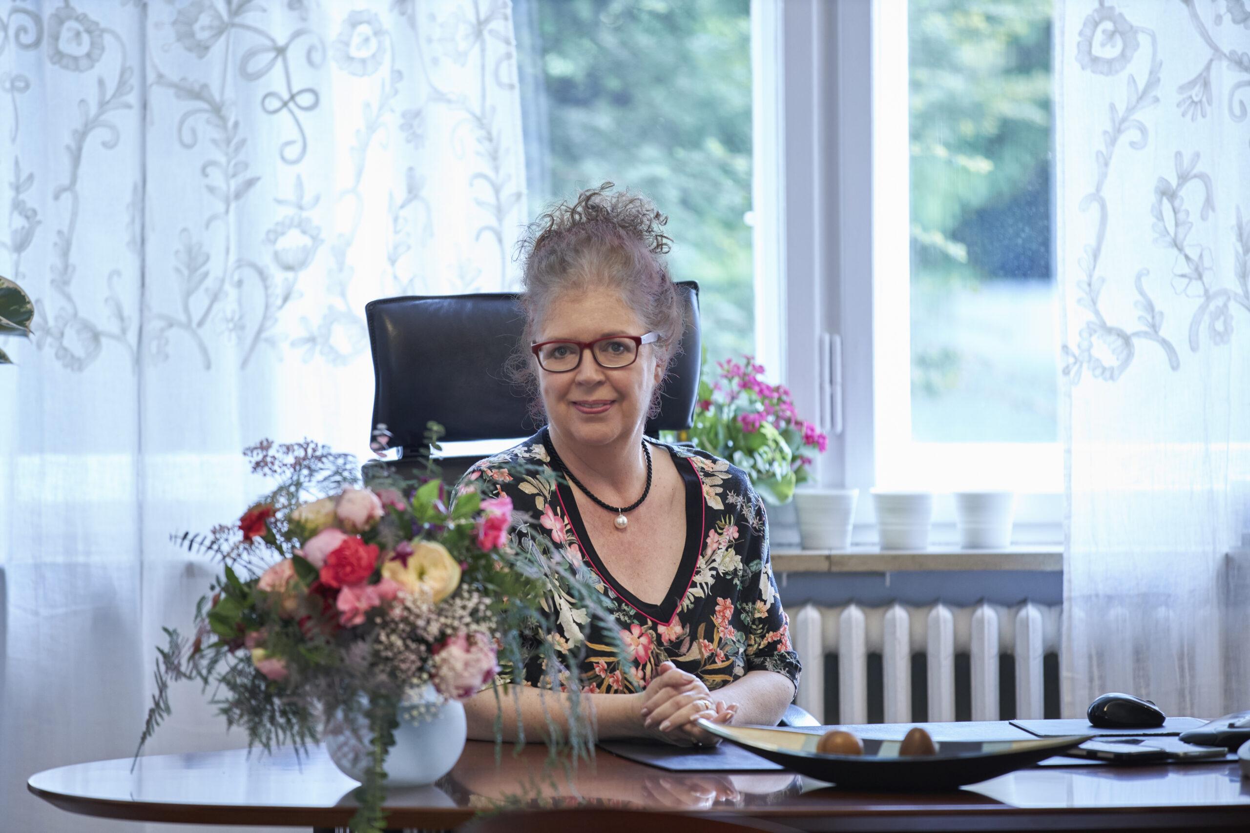 Frau Magret Schneider am Schreibtisch
