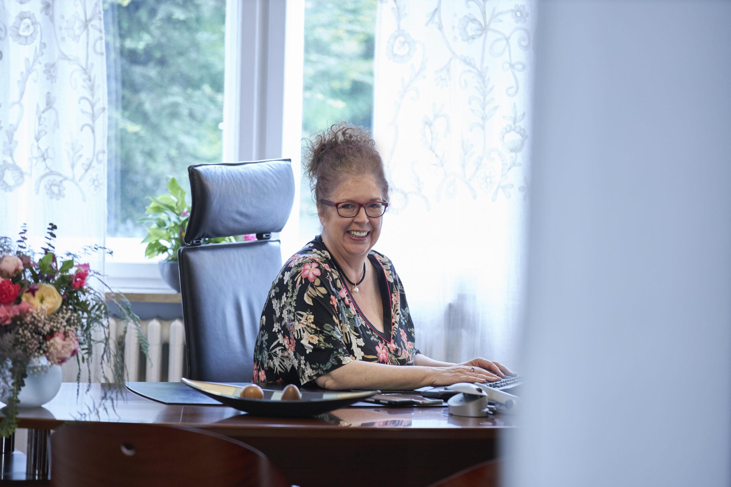 Frau Magret Schneider am Schreibtisch lächelnd